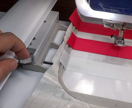 The embroidery hoop with stabilizer and ribbons is locked into the carriage of the Dreamweaver XE. A tutorial on how to make quilt labels using machine embroidery and ribbons using the Brother Dreamweaver XE