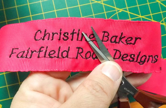 Use small, sharp scissors to trim any excess threads between the letters.  A tutorial on how to make quilt labels using machine embroidery and ribbons using the Brother Dreamweaver XE