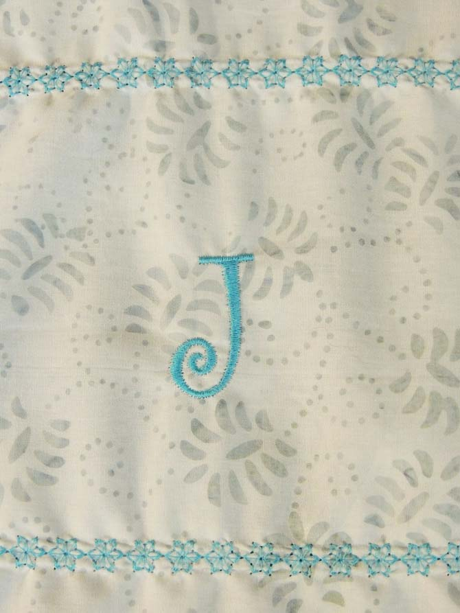 Embroidered letter with two rows of decorative stitches
