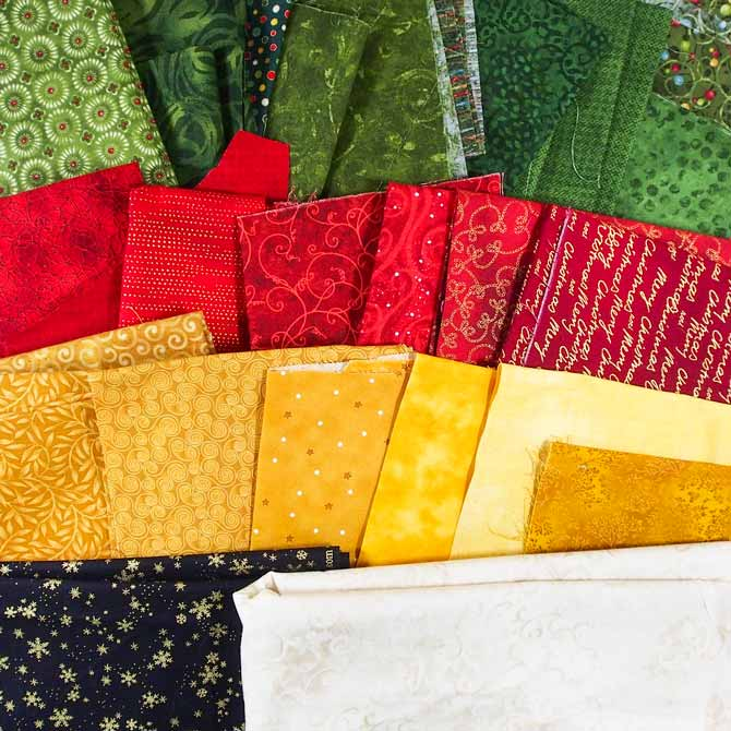 Variety of Christmas fabrics in green, red, gold, cream and black