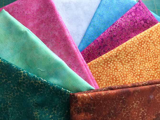 Several pieces of fabric, folded and laid out, in a variety of colors.