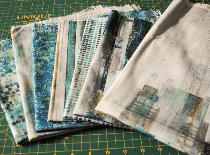 An assortment of Artisan Spirit City Scene fabrics from Northcott fabrics.