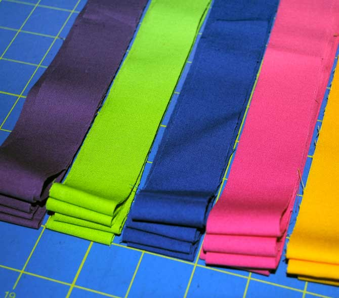 "Twenty 1¼"" strips of solid colored fabrics"
