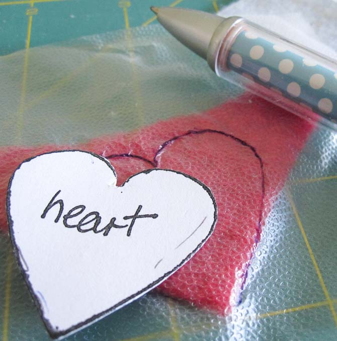 Tracing the heart shape on the food wrap over the red felt wool. WonderFil Specialty Threads.