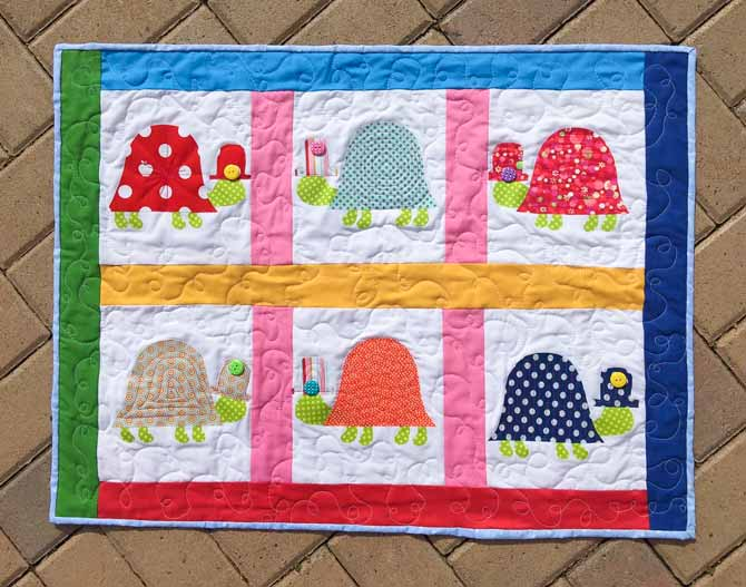 Quilted wall hanging of 6 fused fabric on fabric turtles on a white background with different colored borders and sashing around the turtles.