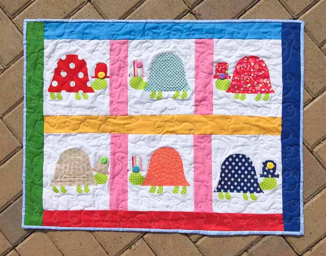 Quilted wall hanging with 6 turtles fused onto a white background, separated by colorful borders and sashing.