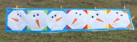 Quilted snowman table runner hanging on a fence in a field.