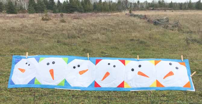 Quilted snowman table runner hanging on fence in a field.