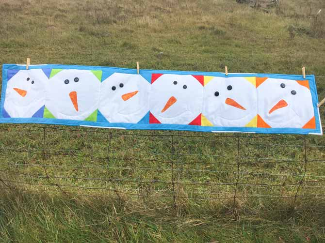Quilted snowman table runner on a fence.