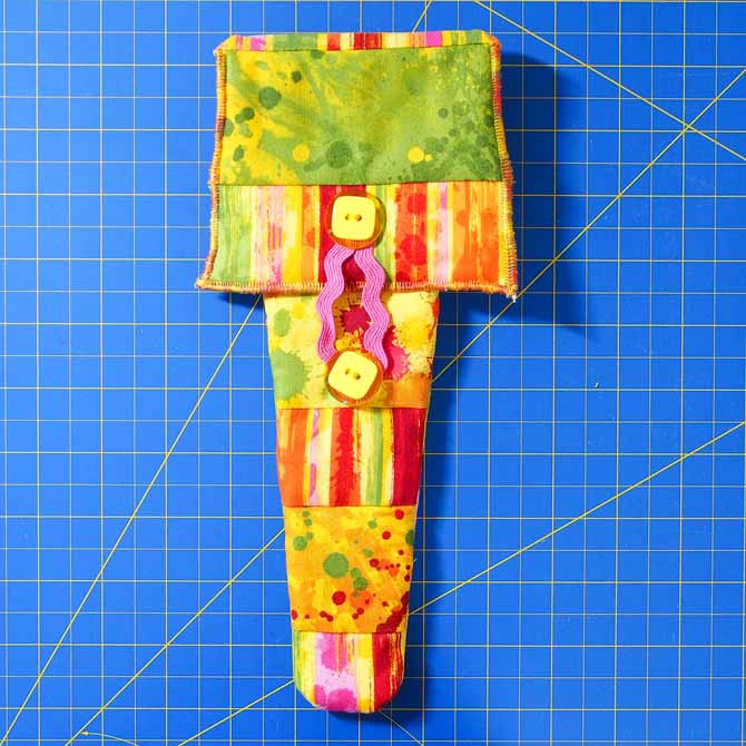 finished quilted scissor holder in bright fabrics with pink rickrack and yellow buttons