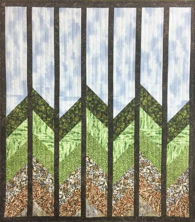 Nature quilt hanging on wall of blues, greens and browns.