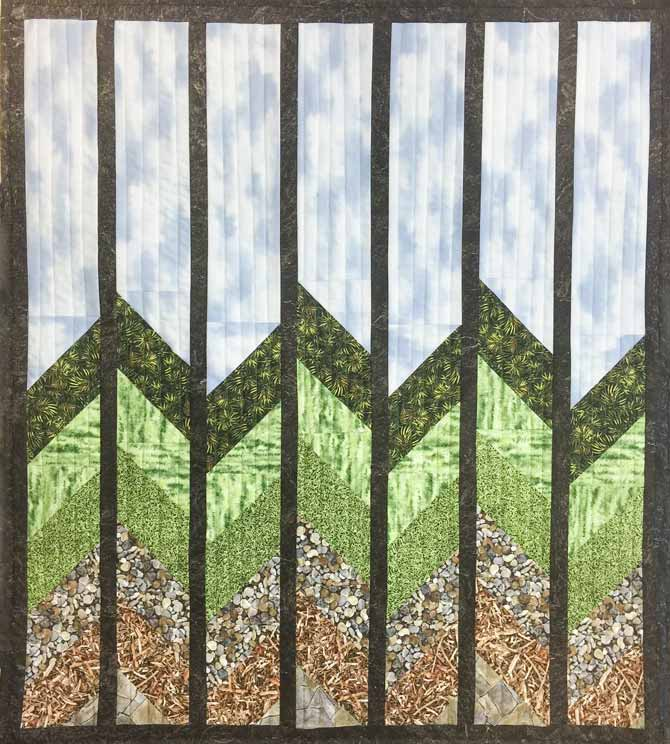 Finished blue and green and brown nature fabric pieced quilt on wall - Northcott's Naturescapes fabric collection
