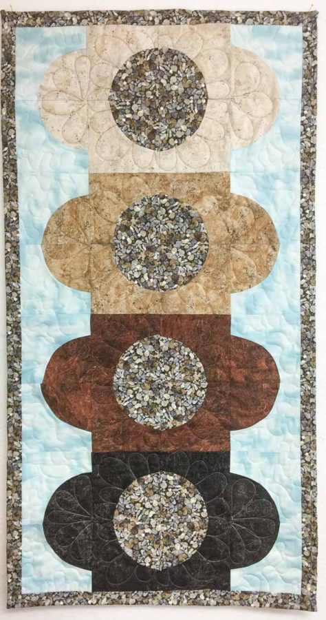 Finished quilt with earth colored fabrics by Northcott Fabrics.