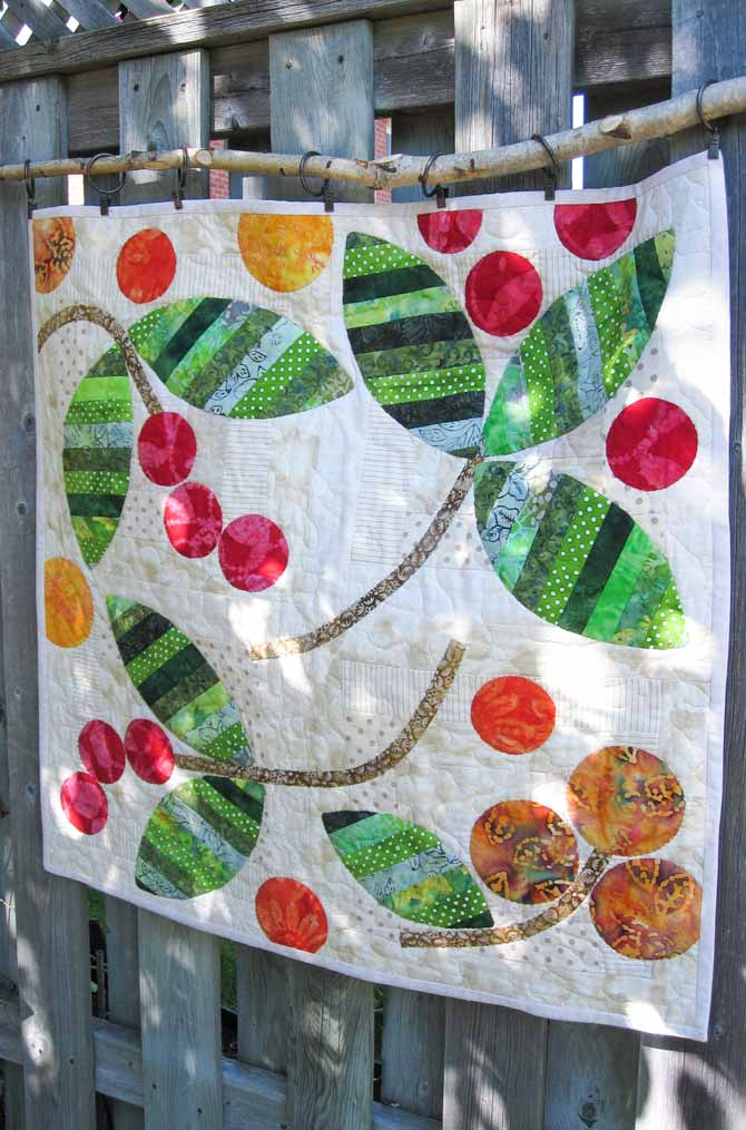 autumn theme quilted wall hanging on a weathered fence