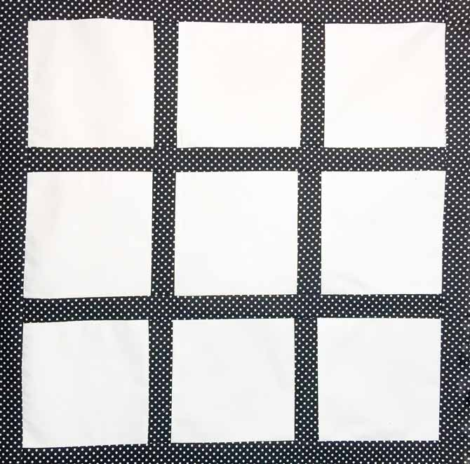 Here is the finished quilt top made with nine white squares with black sashing and borders around it, all made with Northcott's Urban Elementz fabrics