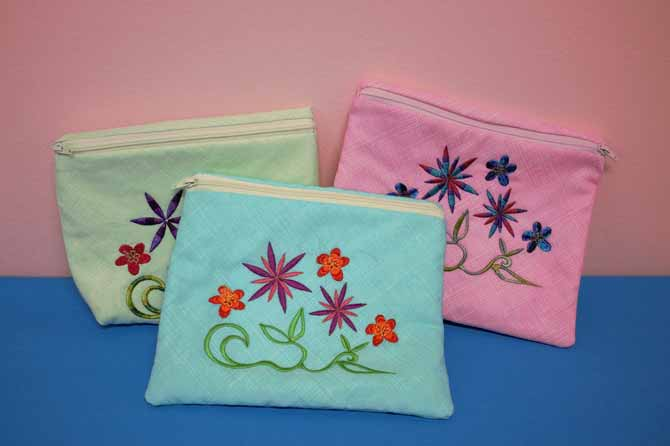 Little zipper bags embellished with machine embroidery stitched with WonderFil's rayon threads.
