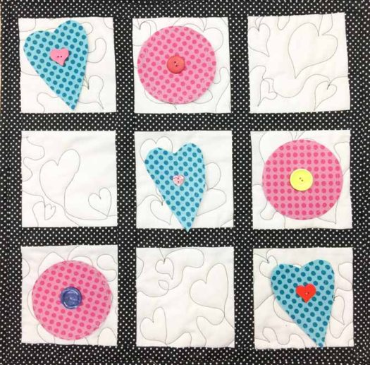 A quilted travel game of 'X's and O's' but in the shapes of hearts and circles, made with Northcott's Urban Elementz fabrics.
