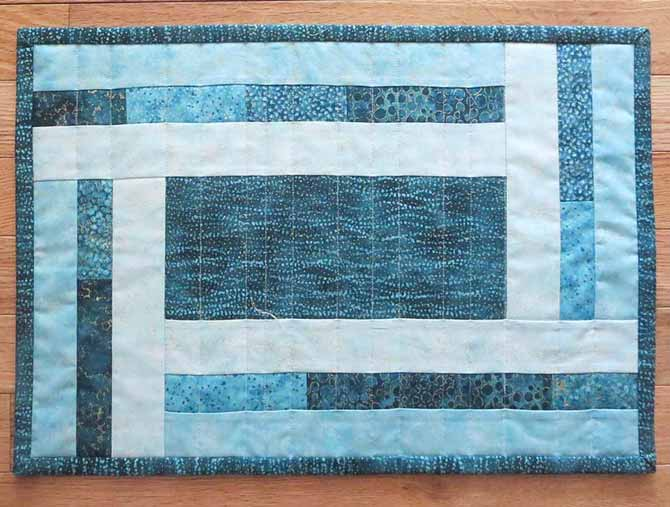The finished placemat, made using Northcott's Artisan Spirit Shimmer and Echoes fabric in the Peacock colorway.