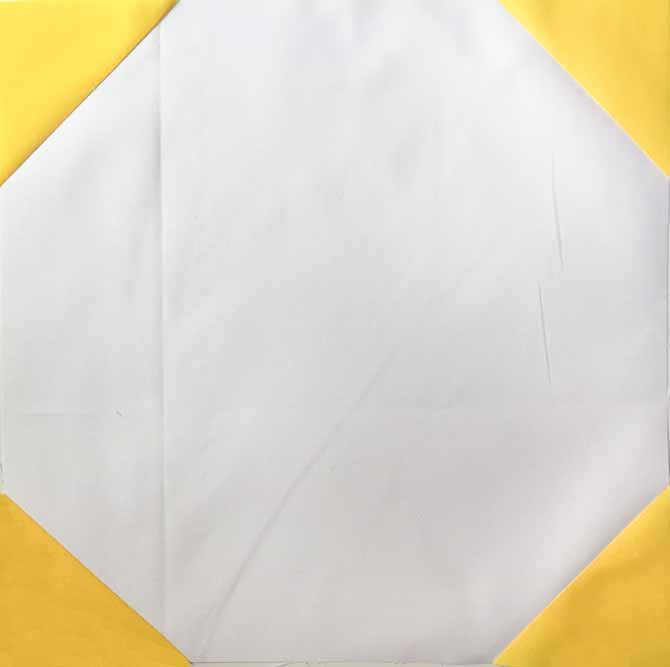 White quilt block with yellow triangles for corners.