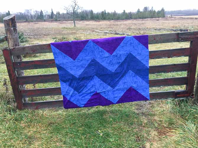 Flannel quilt top of blues and purple draped over a fence in a field.