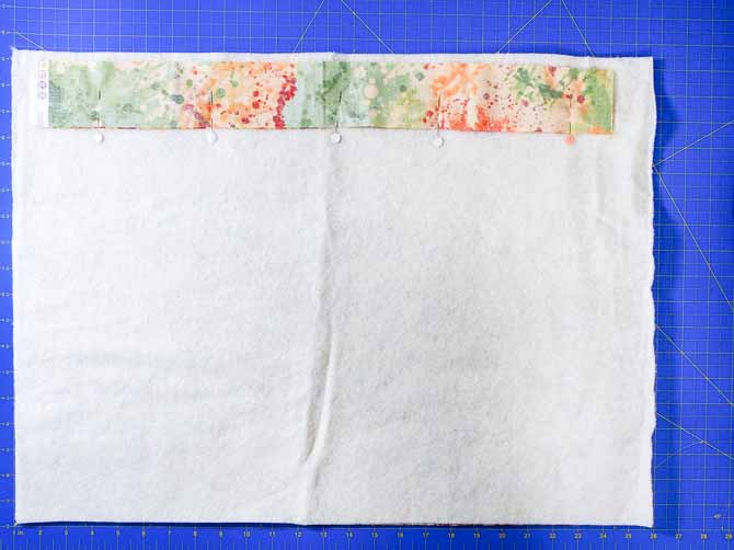 fabric strip pinned to piece of batting on a blue cutting mat