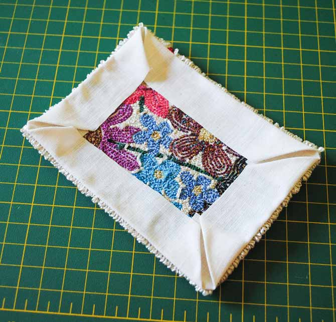 The corners of the weaver's cloth are folded to the back of the punchneedle embroidery that was stitched with Razzle and Dazzle threads.