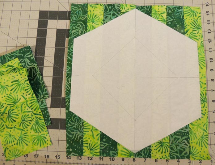 Freezer paper template on top of strip pieced green fabrics.