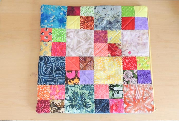 The quilting on the patchwork side of quilted cushion