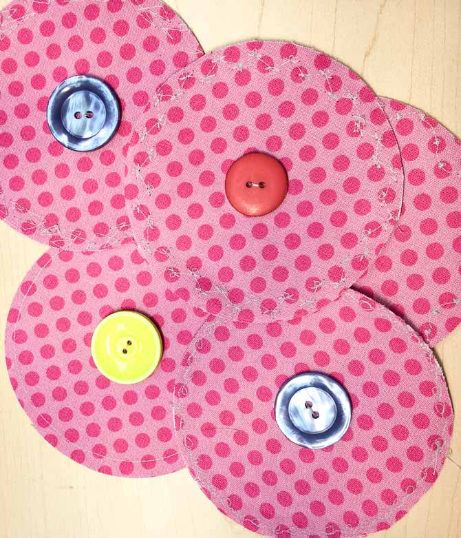 The Urban Elementz pink fabric circles are fused together so their right sides are out and a button stitched in the middle of each circle.