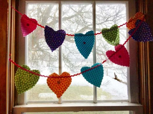 Fabric heart banner of many colors across a window.