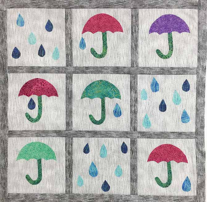 Umbrellas and raindrops against a light gray background completed quilt top with dark gray sashing and borders. Northcott's Artisan Spirit Shimmer Echoes.
