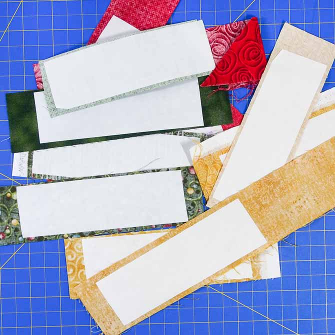 white paper which is fusible web on back of assorted green, red & gold pieces of fabric on a blue cutting mat