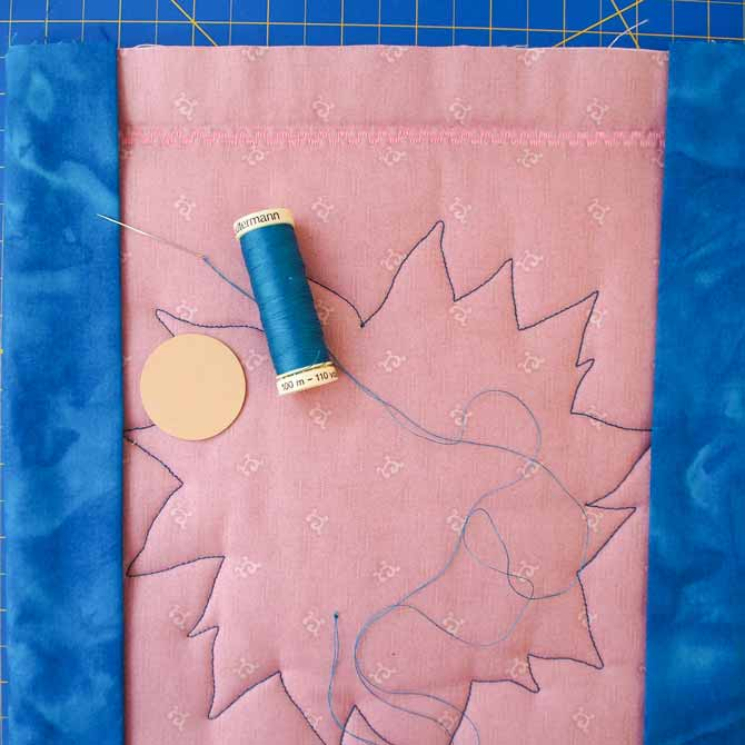 Hand sew facing to back of quilt