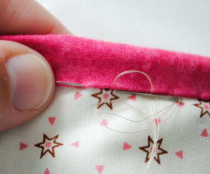 Hand stitching the back of the binding