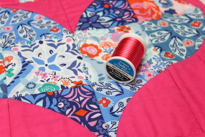 Making beautiful quilting designs using the Sulky Rayon Variables 30wt thread in Vari-Reds. The thread added pizazz immediately on the project.