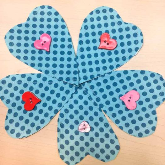 Five fabric heart shapes are made with Northcott's Urban Elementz fabrics and a heart button is sewn to the middle of each shape.