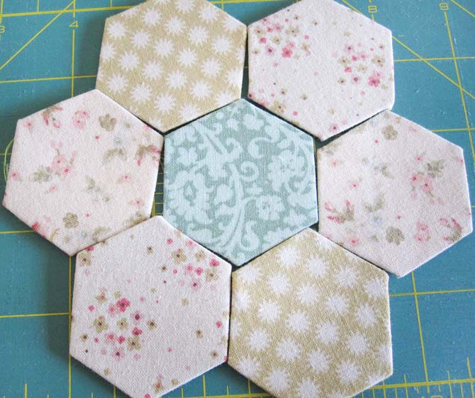 Little English Paper Pieced hexi parts arranged in a flower shape. WonderFil Specialty Threads.