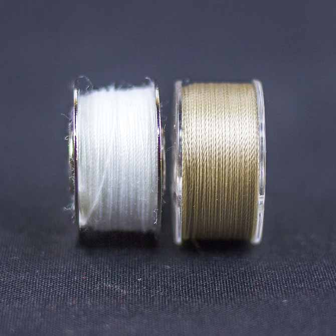 2 bobbins to compare a regular mercerized cotton thread (white) and DecoBob cottonized polyester thread (taupe). WonderFil's DecoBob thread is far more cleaner and lustrous.