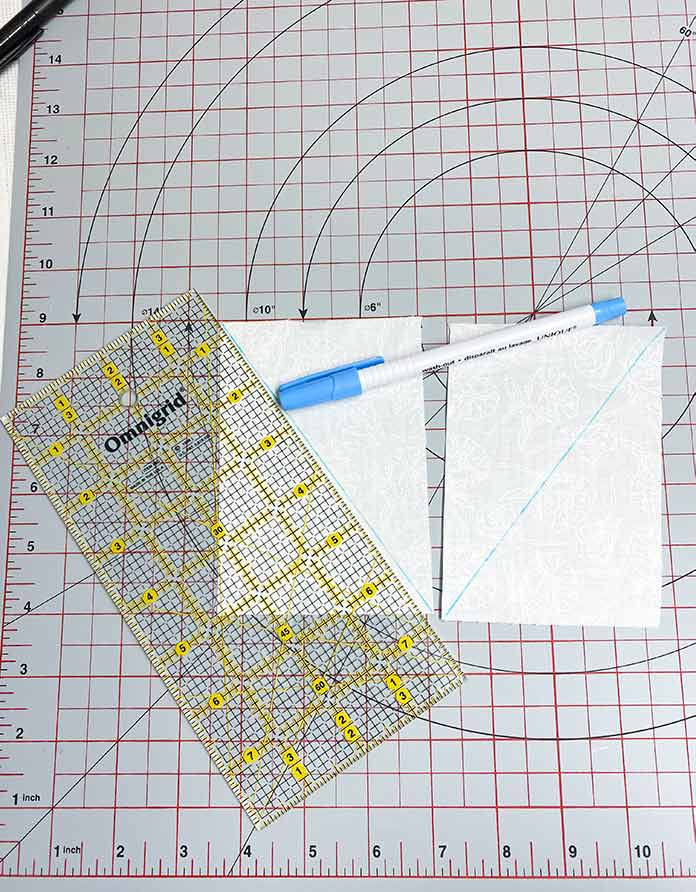 A quilting ruler, a marking pen, and two white fabric rectangles with blue diagonal drawn lines, sitting on a grey cutting mat. SCHMETZ Quilting needles, UNIQUE Sewing Fast Fade Fabric Markers, Omnigrid Rulers, OLFA Rotary Cutter, Komfort Kut Rotating Cutting mat, Fabric Creations Cotton Fabric.