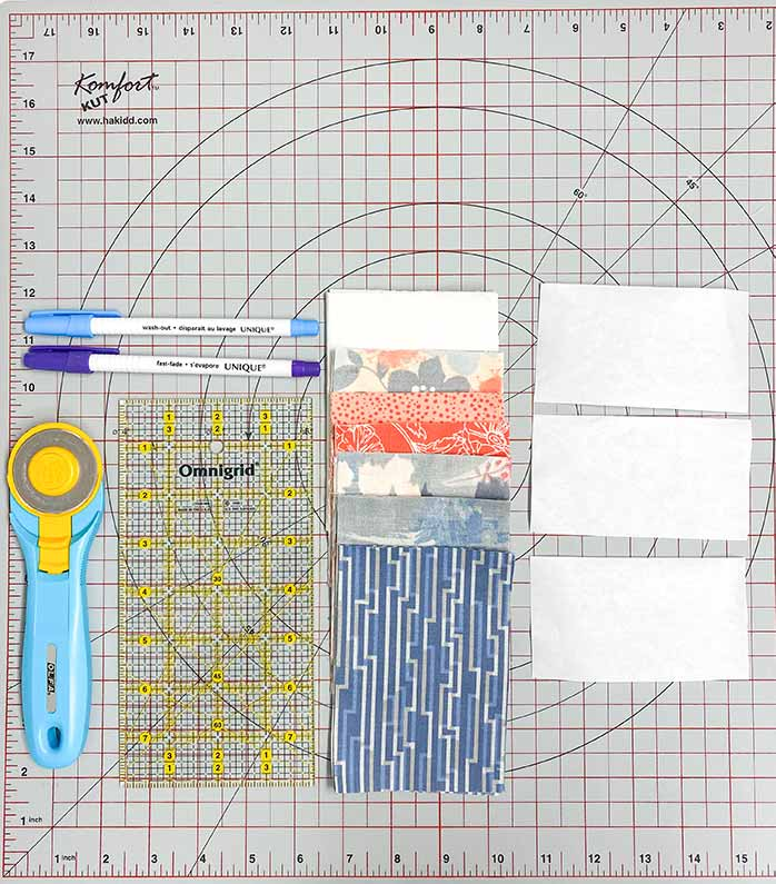 Cut fabric, rotary cutter, quilting ruler, freezer paper and fabric markers on a grey cutting mat. UNIQUE sewing Fast Fade Fabric Markers, Gütermann Thread, SCHMETZ Quilting Needles, Fairfield Quilter's 80/20 Batting, Odif 505 Temporary Quilt Basting Adhesive Fabric Spray, Omnigrid rulers, Olfa Rotary Cutter, Komfort KUT Rotary Cutting Mat, Fabric Creations cotton fabric