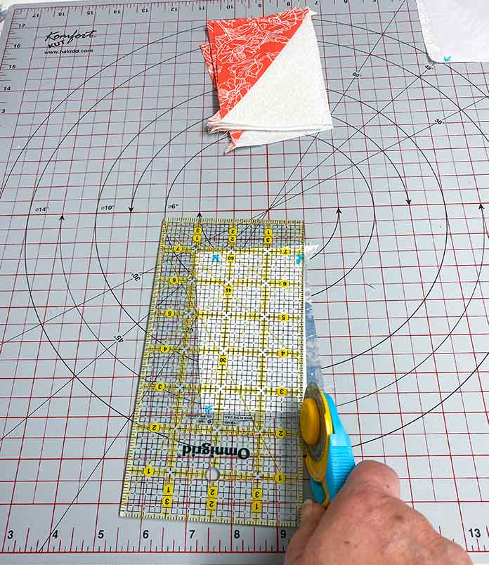 "A Half Rectangle Triangle is trimmed to 2½"" x 4½"" using freezer paper, a rotary cutter, ruler, and rotating cutting mat. Gütermann Thread, SCHMETZ Quilting Needles, UNIQUE Sewing Fast Fade Fabric Marker, Omnigrid Ruler, OLFA Rotary Cutter, Komfort Kut Rotating Cutting Mat, Fabric Creations Cotton Fabric"