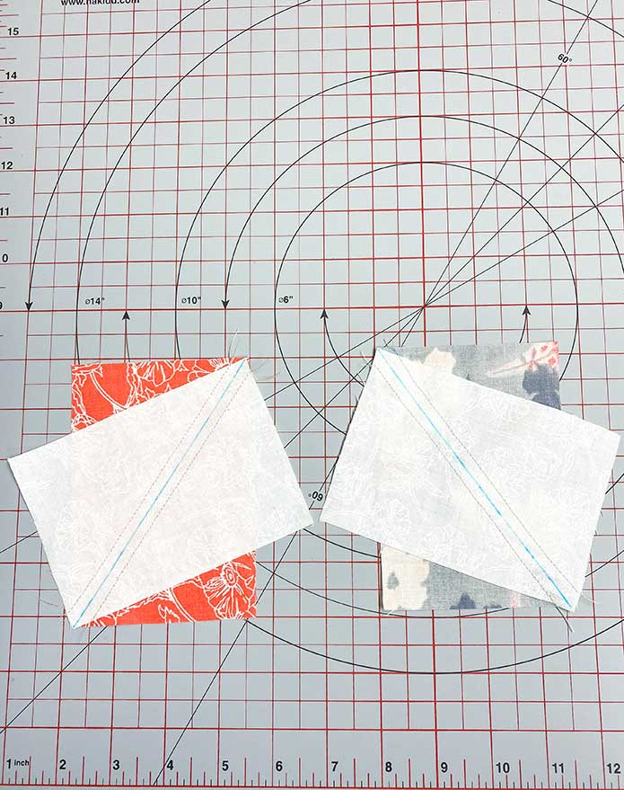 Two white fabric rectangles sewn to two colored fabric rectangles. SCHMETZ Quilting needles, UNIQUE Sewing Fast Fade Fabric Markers, Omnigrid Rulers, OLFA Rotary Cutter, Komfort Kut Rotating Cutting mat, Fabric Creations Cotton Fabric.