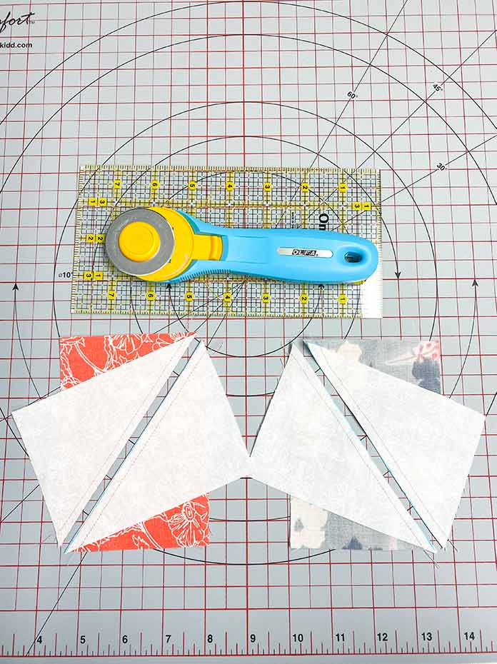 Two sewn rectangle units cut apart to make four Half Rectangle Triangle units. SCHMETZ Quilting needles, UNIQUE Sewing Fast Fade Fabric Markers, Omnigrid Rulers, OLFA Rotary Cutter, Komfort Kut Rotating Cutting mat, Fabric Creations Cotton Fabric.
