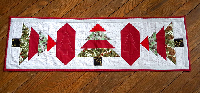 The completed table runner is shown. The three trees were made with a solid red top, light green pinecone layer, followed by dark red and dark green pinecone layers and a brown stump. The trees are divided by a red border with machine-quilted trees on them.