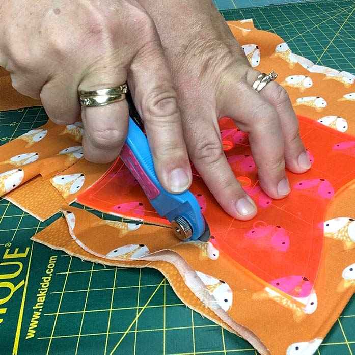 A hand holds down the Twisted Square Template on top of layers of orange fabrics, while the other hand cuts around the template with a rotary cutter.