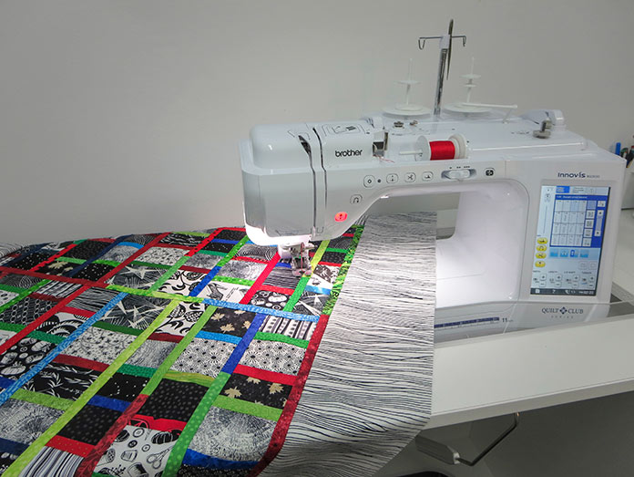 """Finished quilt made from scraps using the Brother Innov-ís BQ3050 machine. Brother Innov-ís BQ3050 sewing and quilting machine, Mary Ellen's Best Press, Brother SA185 ¼"""" Piecing Foot with Guide, Brother SA125 ¼"""" Quilting Foot, Olfa square ruler, MuVit digital dual feed foot"""