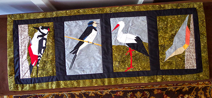 A quilted table runner with birds on it