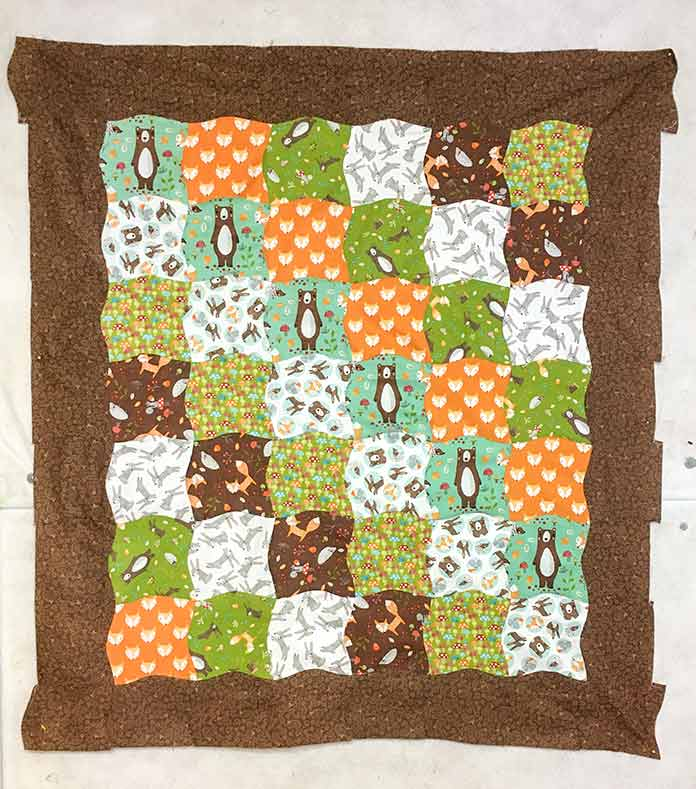 The quilt made with the Twisted Square Template by Sew Easy now has a curved brown border.