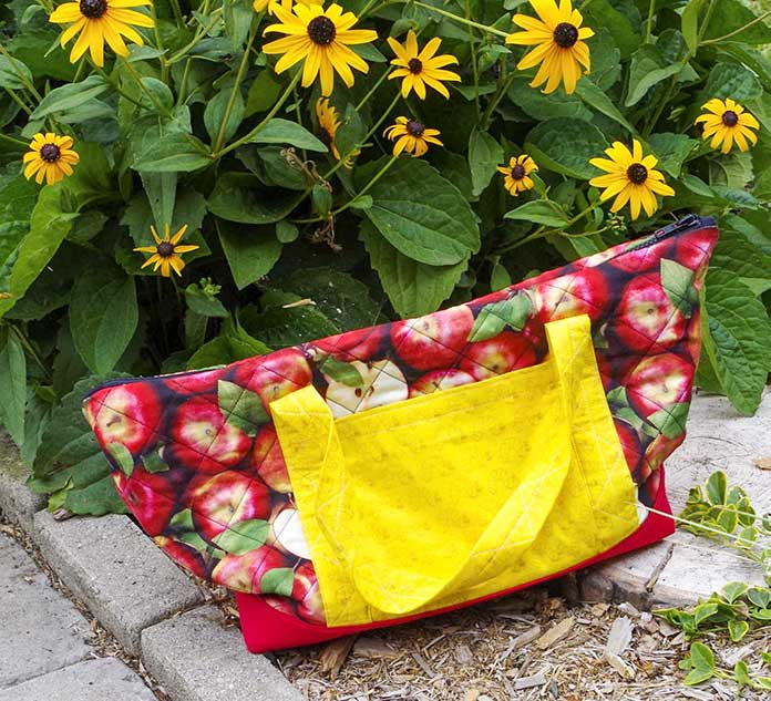 This is a side view of the completed bag sitting in the garden in front of some yellow flowers. The main bag is made of apple fabric, you can see the yellow worm straps and one pocket, the black zipper and a little bit of the red bottom of the bag.