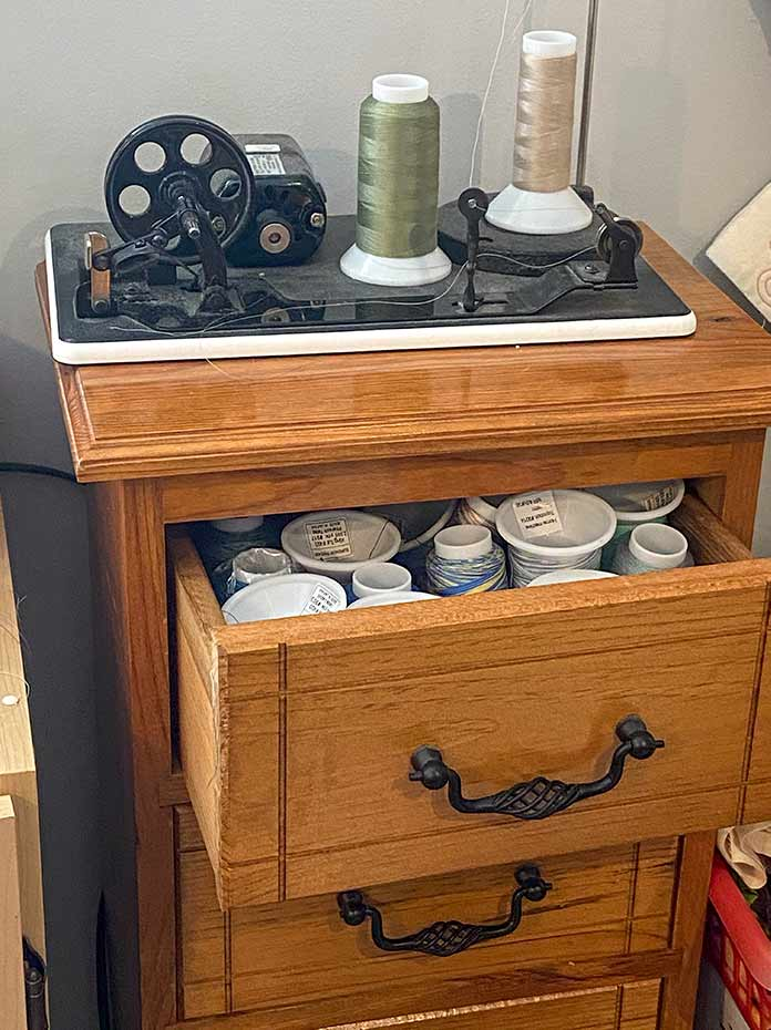 This handmade wooden cabinet has deep drawers that can hold up to 12 large cones of threads. The top is large enough to house the bobbin winder for the longarm quilting machine.